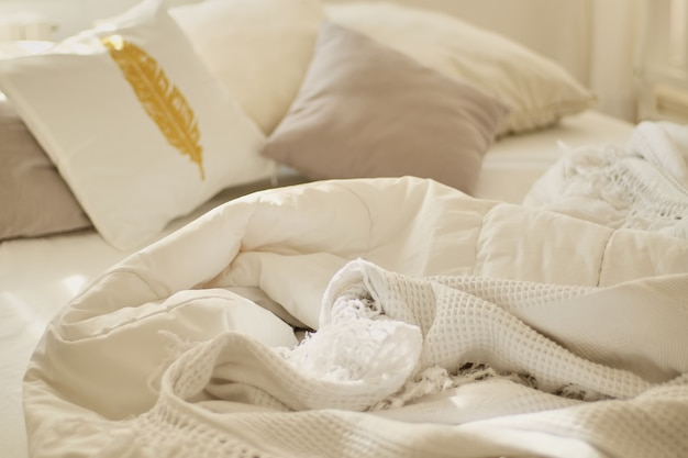 Rommelig bed. wit hoofdkussen met deken op onopgemaakt bed. concept van ontspannen na de ochtend.