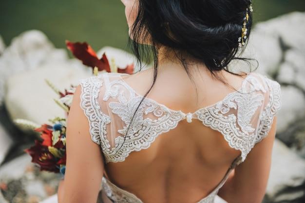 Rommelig bruids opgestoken kapsel met elegante haarspeldjuwelen, open rugjurk, donker haar
