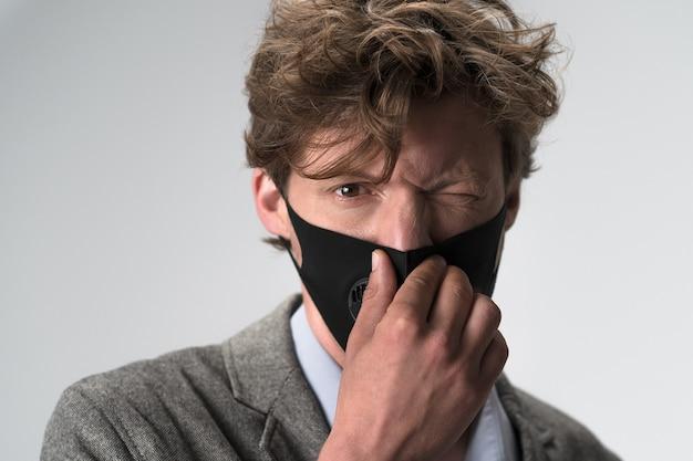 Rommelig haar knappe jongeman in grijs jasje en een modern herbruikbaar beschermend masker op zijn gezicht voelt
