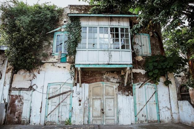 Rommelige gevel van een oud gebouw met wilde plant op muur en raam