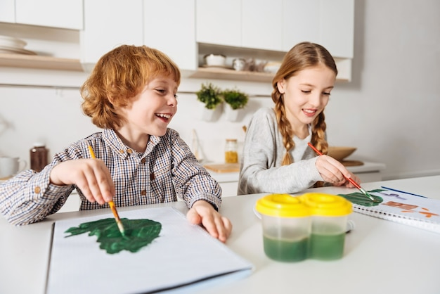 Rommelige meesterwerken. charmante creatieve schattige broers en zussen die plezier hebben in het schilderen met aquarellen terwijl ze het weekend samen thuis doorbrengen