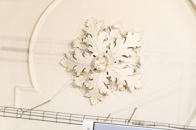 Rond antiek vintage decoratief kleistucwerkreliëf met bloemenornamenten op wit plafond in abstract klassiek interieur