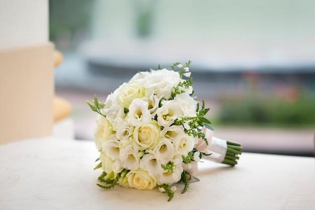 Rond bal bruidsboeket van witte bloemen, witte rozen en eustomas