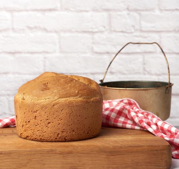 Rond brood gebakken in een elektrische broodbakmachine en een emmer voor het kneden van deeg