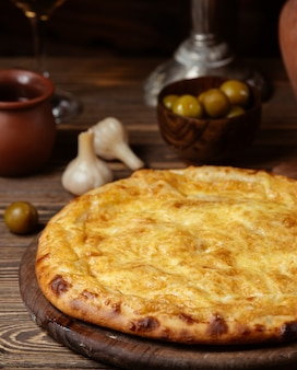 Rond brood met gesmolten kaas erop