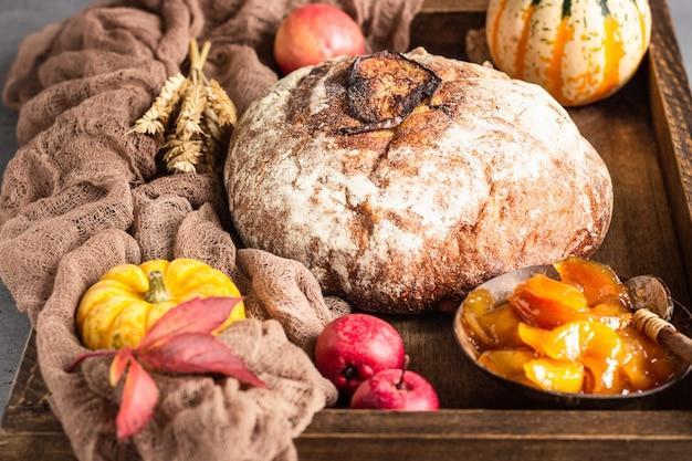 Rond brood van artisanaal tarwebrood met pompoen en appel in een houten dienblad.