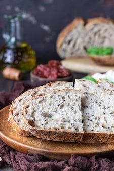 Rond brood van vers gebakken zuurdesembrood met ricottakaas, gedroogde tomaten, basilicum en olijfolie.