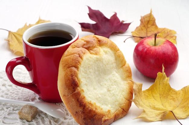 Rond broodje met kwark en kopje thee op tafel