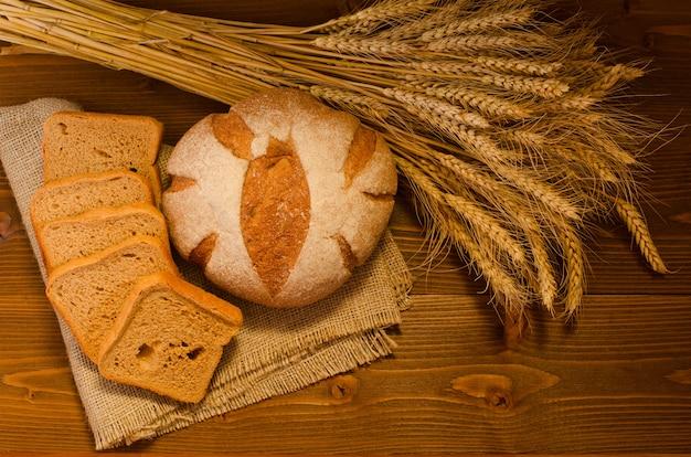 Rond en vierkant roggebrood op een plundering, een schoof op houten tafel