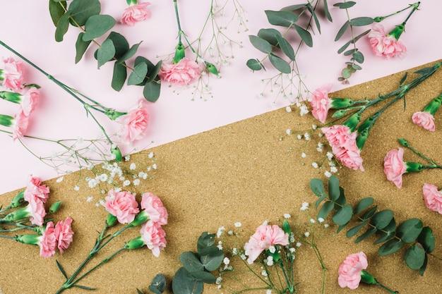 Rond frame gemaakt met gypsophila en roze anjerbloemen op dubbele roze en kartonnen achtergrond
