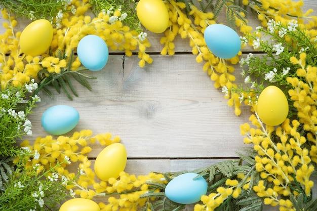 Rond frame gemaakt van mimosa takken en paaseieren op houten planken