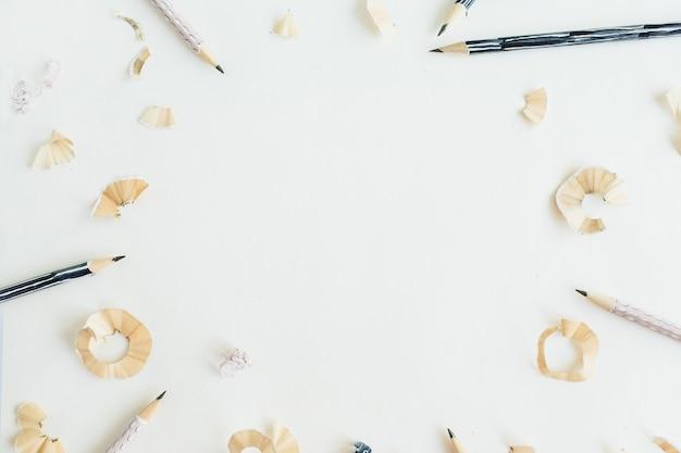 Rond frame van potloden en krullen op wit oppervlak