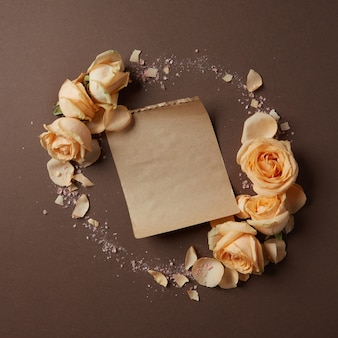 Rond frame van rozen op een bruine achtergrond met een stuk papier voor uw tekst, plat gelegd