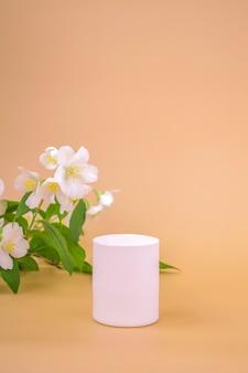 Rond hoog podium om cosmetica, producten op een beige achtergrond en jasmijn te presenteren