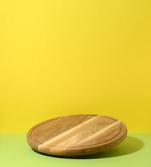 Rond houten keukenpizzabord op geelgroene achtergrond, gebruiksvoorwerpen zweven
