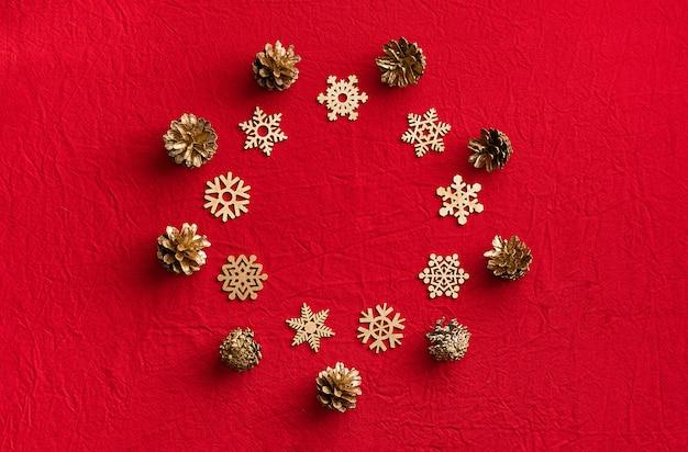 Rond kader van houten sneeuwvlokken en denneappels op een rode achtergrond. kerstmis nul afvalconcept. plat leggen.