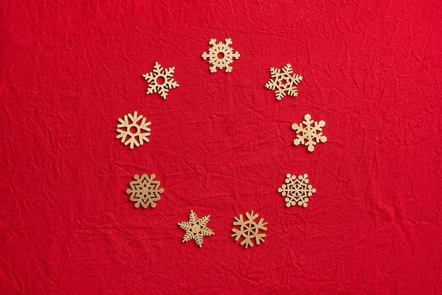 Rond kader van houten sneeuwvlokken op een rode achtergrond. kerstmis nul afvalconcept. plat lag, bovenaanzicht.