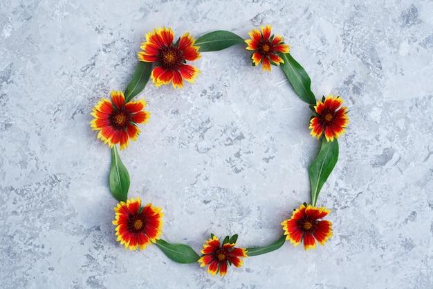 Rond kader van verse oranje bloemen, op een grijze achtergrond. lichte textuur met bloemstuk, copyspace. bovenaanzicht, platliggend. herfst concept
