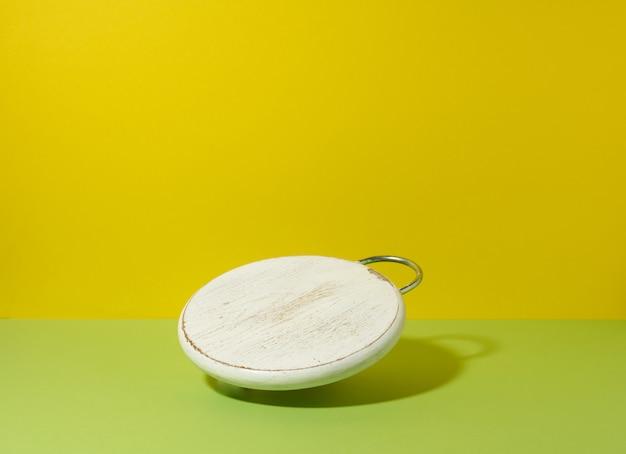 Rond leeg wit houten keukenbord op geelgroene achtergrond, gebruiksvoorwerpen zweven