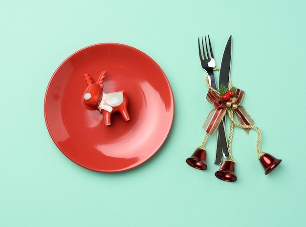 Rond rood ceramisch plaatmes en vork op feestelijke lijst die voor kerstmis plaatsen