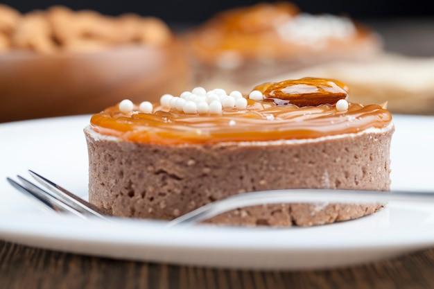 Rond taartje met kwarkroom bedekt met romige karamel erop, dessert gemaakt van deeg en zuivelproducten in karamel