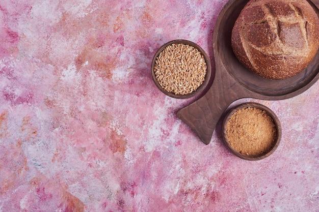 Rond zelfgebakken brood met gemengde tarwe opzij, bovenaanzicht.