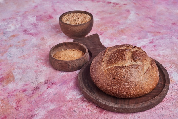 Rond zelfgebakken brood met gemengde tarwe opzij.