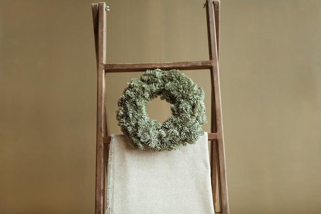 Rond zelfgemaakt kransframe gemaakt van sparrennaalden tegen olijfmuur. kerstviering decoratie