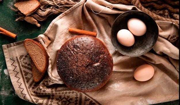 Rond zwart brood met plakjes, kaneel en eierkom op een groene tafel.