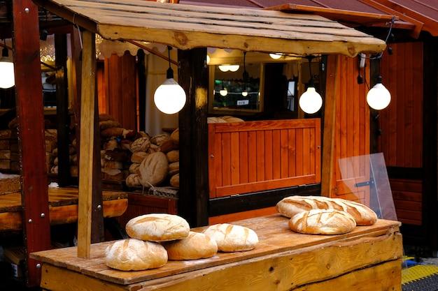 Ronde baguettes van vers gebakken wit brood op een houten tafel op de markt.