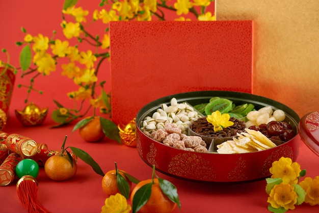 Ronde blikken doos met gedroogde vruchten, noten, geroosterde meloenzaden, crackers met beste wensen inscriptie en mandarijnen voor maannieuwjaarsviering