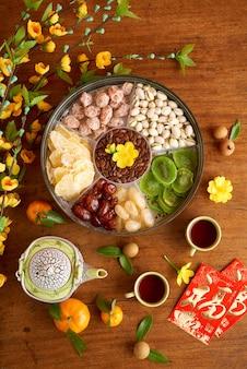 Ronde blikken doos met zoete gedroogde vruchten, noten en gebakken meloenzaden, theekopjes en kaarten met de beste wensen inscriptie voor de viering van het nieuwe maanjaar