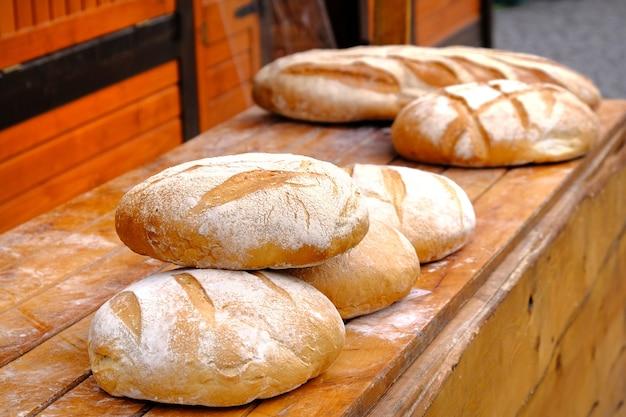 Ronde broodjes van vers gebakken wit brood op een houten lijst aangaande voedselmarkt.
