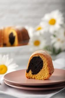 Ronde cupcake met een gat op een witte schaal bestrooid met poedersuiker