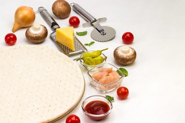 Ronde deegbodem voor pizza en diverse ingrediënten