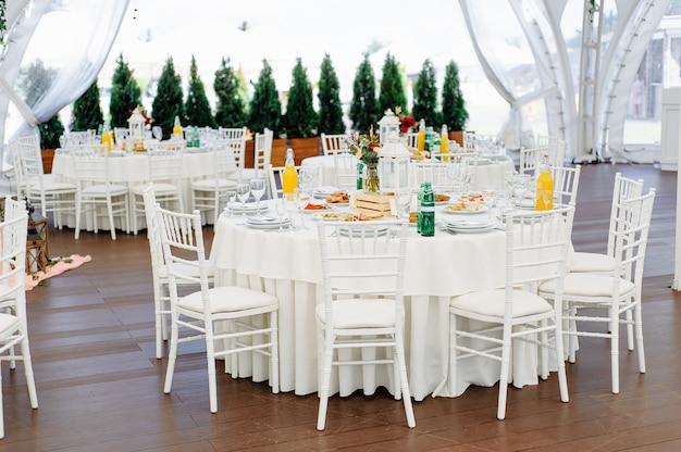 Ronde dinertafels bedekt met blauwe stoffen standaard in een wit huwelijkspaviljoen
