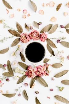 Ronde frame krans patroon met rozen, koffiekopje, roze bloemknoppen, takken en gedroogde bladeren op wit oppervlak