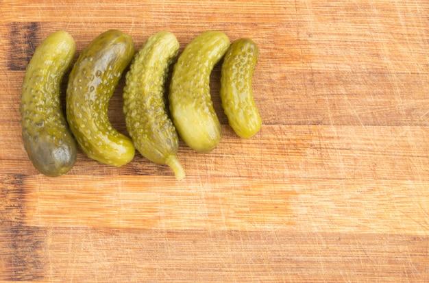 Ronde frame van zelfgemaakte augurken met kopie ruimte. gemarineerde komkommers op rustieke houten achtergrond