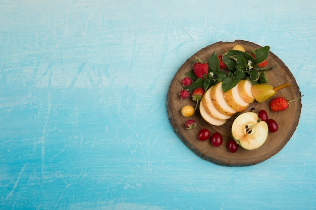 Ronde fruitschaal met peren, appel en bessen aan de rechterkant