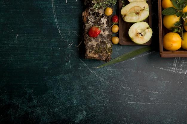 Ronde fruitschaal met peren, appel en bessen op matte achtergrond