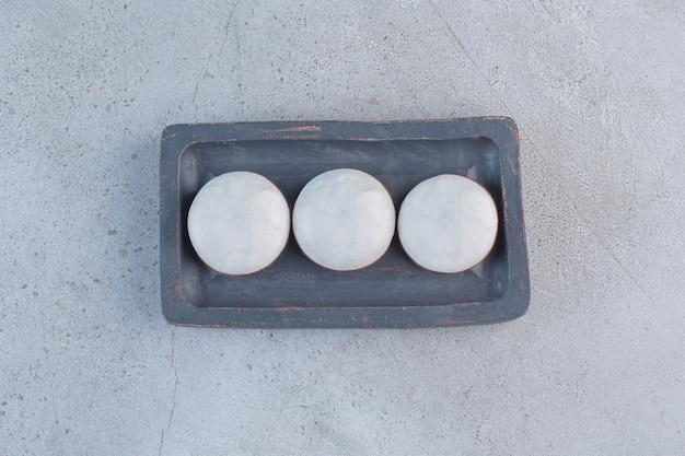 Ronde geglazuurde koekjes op zwarte plaat op stenen ondergrond.