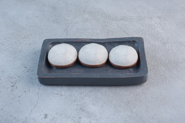 Ronde geglazuurde koekjes op zwarte plaat op stenen tafel.
