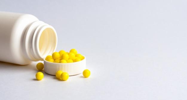 Ronde gele vitamines worden uit een witte plastic fles op een witte glanzende tafel gegoten. concept. plaats voor het label. diagnose.