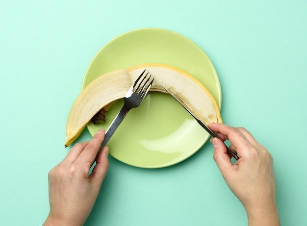 Ronde groene keramische plaat met een hele banaan twee handen houden een mes en een vork vast