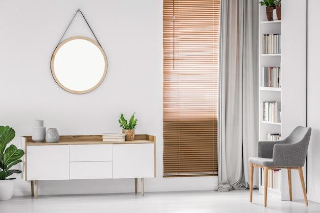 Ronde hangende spiegel aan de witte muur boven een kast in een licht eigentijds kamerinterieur. echte foto.