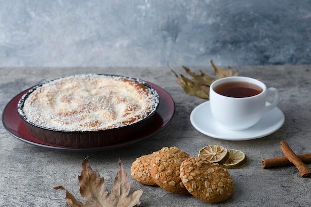 Ronde heerlijke cake met een kopje thee op een marmeren tafel.