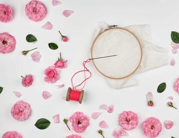Ronde houten hoepel en rode draad met naald