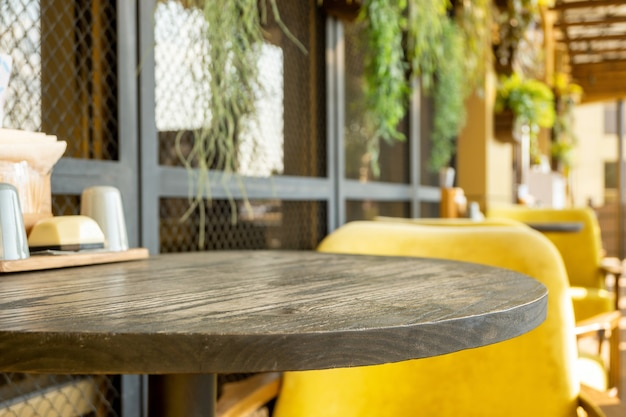 Ronde houten tafel en gezellige gele stoel in straatcafé. leeg restaurantmeubilair op het terras buiten.