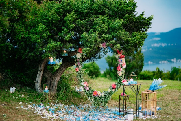 Ronde huwelijksboog van bloemen en olijftakken die op hangen