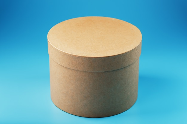 Ronde kartonnen doos op een blauwe achtergrond, vrije ruimte.